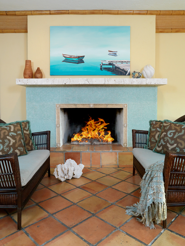 A breezy ocean view home with beach glass tile and coral rock Fireplace mantel