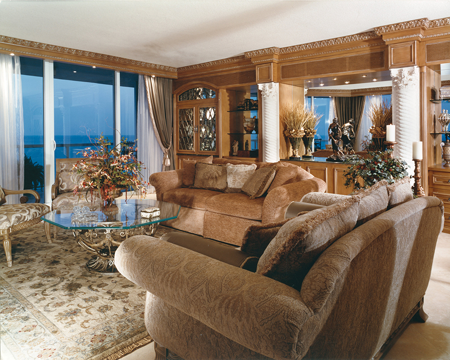 A Tuscan Living Room with custom wall unit in distressed wood and wrought iron glass doors.