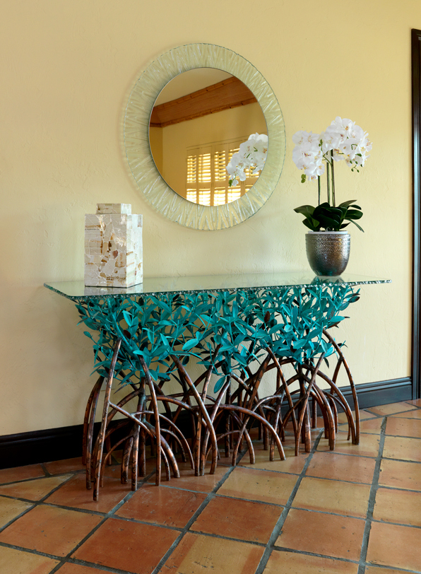 An Oceanside foyer with a copper mangrove console table and wavy framed mirror