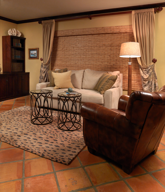 A comfortable study with sofa bed, leather chair and animal print rug.