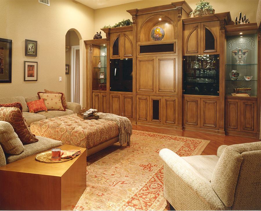 Custom wall unit in walnut and etched glass panels graces a large family room with rust and tan oriental rug